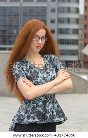 Red-haired woman posing on the office building background - stock photo