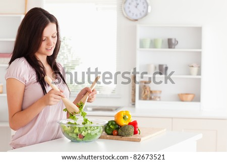 Red-haired woman preparing a salad in a kitchen