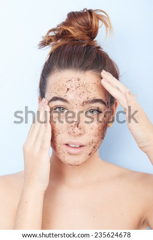 Red-haired woman with a scrub applied on her face - stock photo