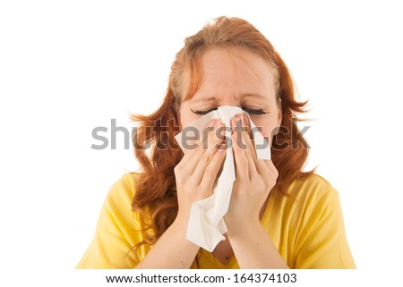 Red haired woman with yellow shirt blowing nose isolated over white background