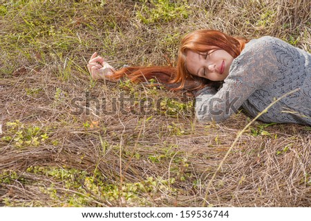 red haired women lying on autumn grass