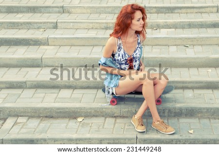 Red haired women sitting on skateboard and looking away,a lot of copyspace. Redhair teen girl sitting on her skateboard against street stairs. Pensive feelings. Street fashion. Thoughtful teenager. - stock photo