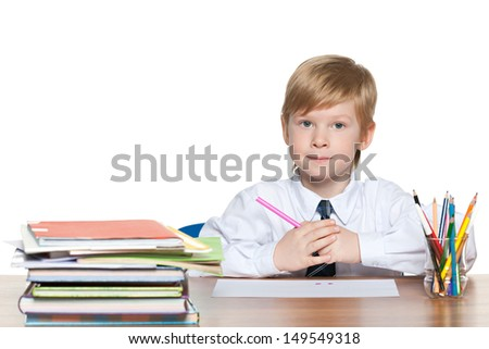 Red-haired young boy is sitting at the desk