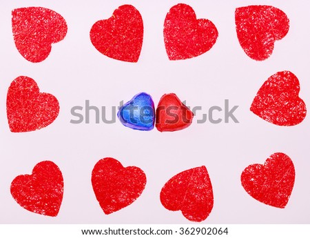 Red handmade hearts with two chocolate hearts candies on pink texture background. Greeting card on Valentines day. - stock photo