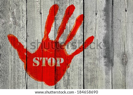 Red handprint with the word ''Stop'' on old wooden fence background - stock photo