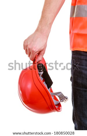 Red hard hat in hands of man construction worker builder foreman in orange safety vest isolated on white. Safety in industrial work. Studio shot.