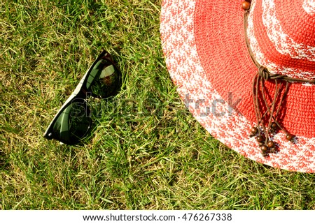 Red hat and sunglasses on the grass