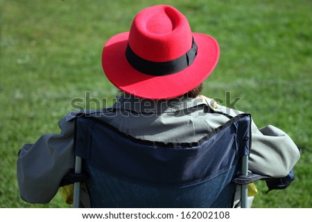 Red hat lady in a sports chair. - stock photo