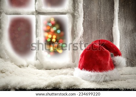 red hat on wooden sill of window and snow decoration on frame  - stock photo