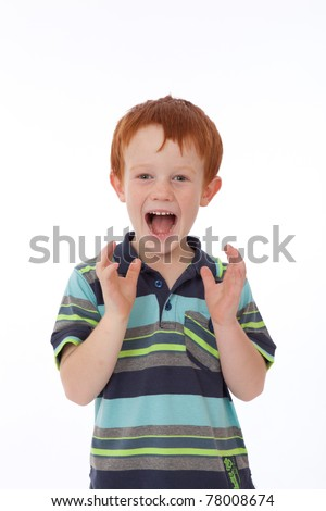 Red head boy with freckles looking shocked and surprised while smiling and holding hands in air
