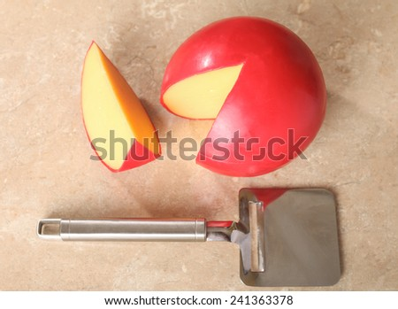 Red head cheese and cheese knife on the table - stock photo