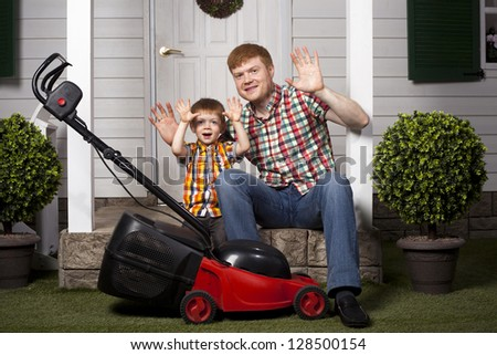 red head father and son sitting on the porch of country house with lawn mower