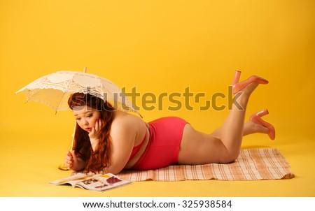 Red head plus size model under the sun umbrella reading magazine in studio  - stock photo