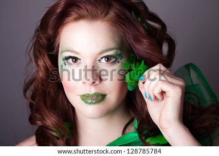 Red headed Beautiful woman  with a shamrock wearing exotic green makeup