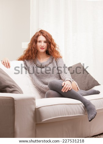 Red Headed very cute girl self-confident on her sofa in her living room - stock photo
