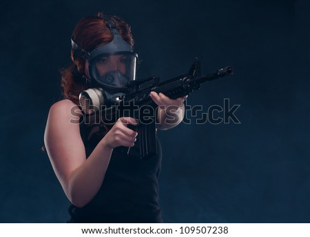 Red headed woman in a gas mask aims her M16 ready to fire as she emerges from the smoke - stock photo