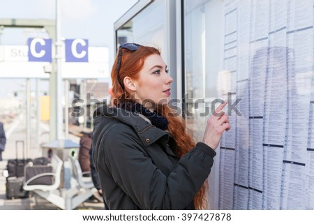 Red headed young woman at a train station wearing a coat reads board covered with transportation timetables - stock photo