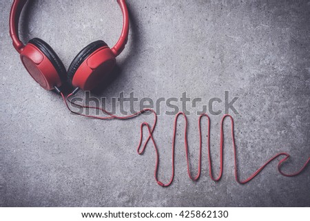 Red headphones on stone background