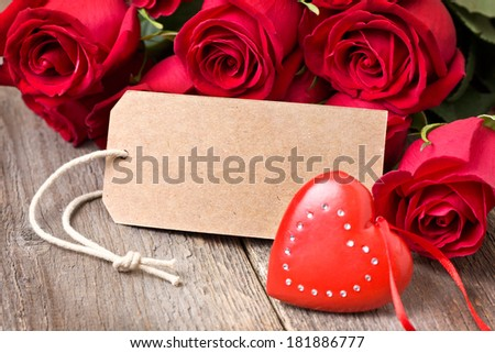 red heart and a bouquet of red roses on a wooden background