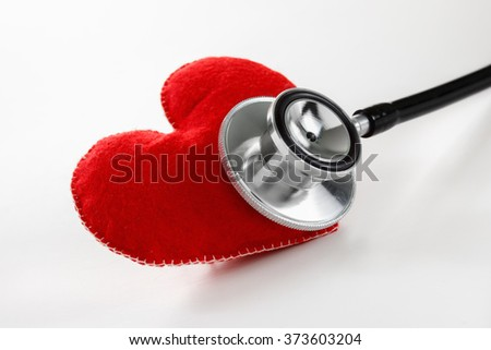 Red heart and a stethoscope. Healthcare and Medicine concept studio shot. On white background. - stock photo