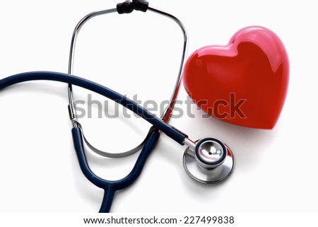 Red heart and a stethoscope lying at the desk, isolated on white background - stock photo