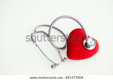 Red heart and a stethoscope on white floor background