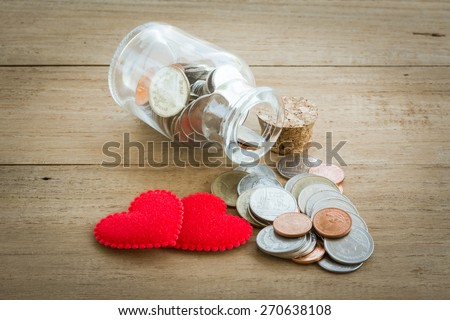 red heart and coin on the wooden table - stock photo