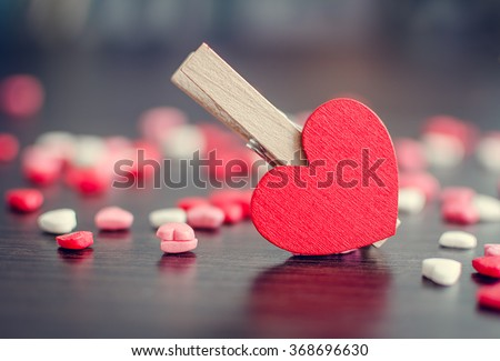 Red heart and many small hearts on blurred background. Valentines Day background. Valentine's Day theme. Selective focus, closeup, horizontal. Toned image. - stock photo