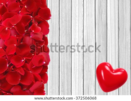 red heart and rose petals on white wooden background  - stock photo