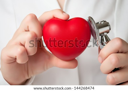 Red heart and stethoscope in a doctor's hand - stock photo
