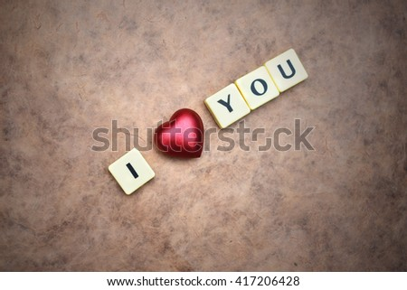 red heart and words i love you on a vintage  paper background. concept