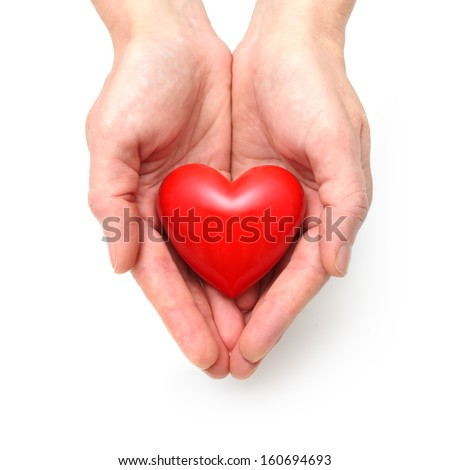 Red heart at the human hands isolated on white