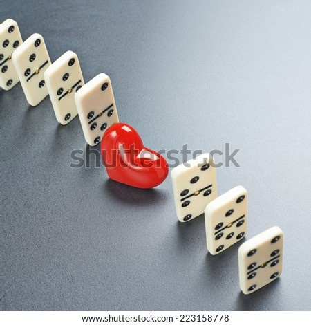 Red heart between the the white domino pieces over the dark gray surface - stock photo