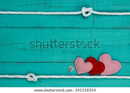 Red heart, candy cane striped hearts and silver lock by white rope with knot border on blank antique teal blue old weathered background - stock photo