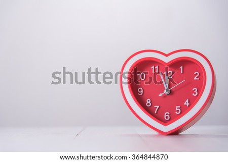 red heart clock on white wooden table - stock photo