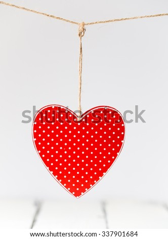 Red heart decoration with white dots hanging - stock photo