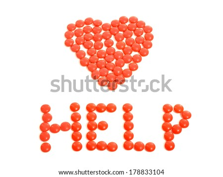 Red heart drugs. Pills arranged in heart shape with help sign. Close up on pills isolated on white background.