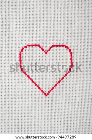 red heart embroidered in cross stitch on white canvas - stock photo