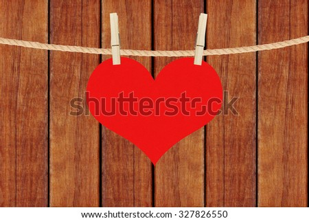 red heart hang on clothespins over brown wooden planks background - stock photo