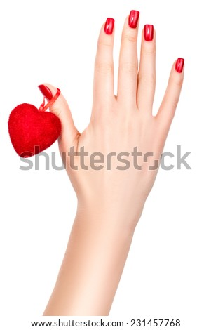 Red heart hanging on a female hand.