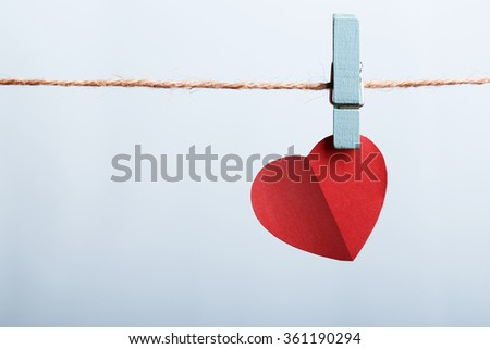 Red heart hanging on line against blank background. - stock photo