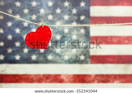 Red heart hanging on rope clothesline in front of antique rustic American canvas flag blurred in background - stock photo