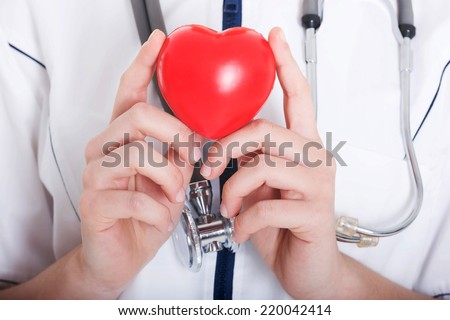 Red heart held by a female doctor. Close up. - stock photo