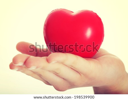 Red heart held on a female's hand