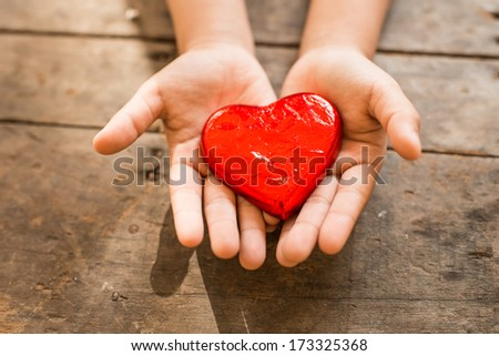 Red heart in child's hands - stock photo