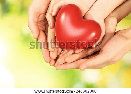 Red heart in family hands on bright background