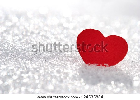Red heart in glittering snow with shallow depth of field - stock photo
