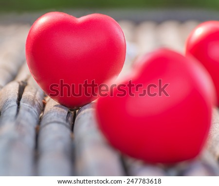 Red heart in love of Valentine's day with wood background.