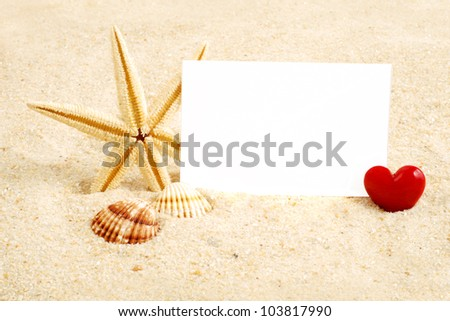 Red heart in sand, with card