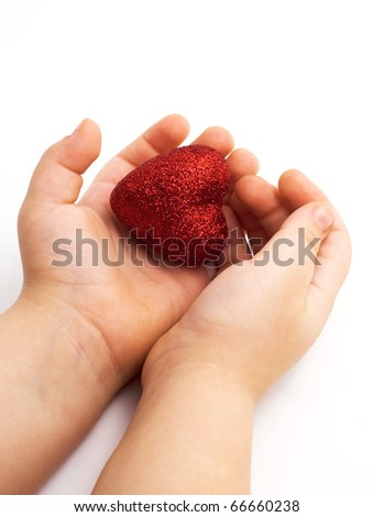 red heart in the children's arm, white background - stock photo